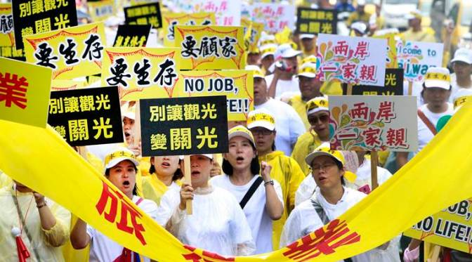 Tourism-related business workers shout slogans during a march in Taipei, Taiwan, Monday, Sept. 13, 2016. Thousands of tourism-related business workers held a march to call for the government''s attention on the decline of mainland Chinese visitors since President Tsai Ing-wen took office in May. It''s believed that Beijing might have taken the action to tighten its control over Taiwan-bound tourist arrivals after Tsai refused to endorse the concept of a single Chinese nation. (AP Photo/Chiang Ying-ying)